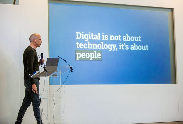 User experience expert Paul Boag stands in front of a slideshow, which says 'Digital is not about technology, it's about people'.