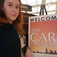 Data Journalist Sophie Warnes standing next to the NICAR conference board